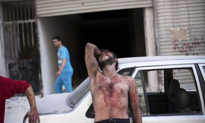 In this Thursday, Oct. 4, 2012 file photo, a Syrian man cries outside the Dar El Shifa hospital in Aleppo, Syria after his daughter was injured during a Syrian Air Force strike over a school where hundreds of refugees had taken shelter. Syria's uprising was not destined to be quick.  (AP Photo/ Manu Brabo)