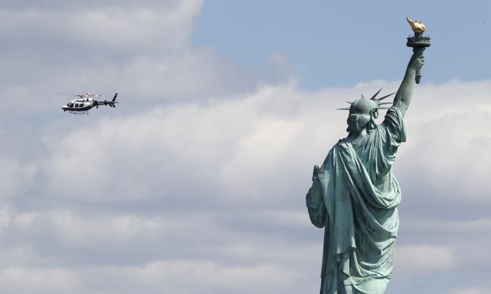 A New York Police helicopter circles over  Liberty Island where the Statue of Liberty was evacuated with officers responding to a report of a suspicious package, seen from Jersey City, N.J., on April 24, 2015. (AP Photo/Julio Cortez)