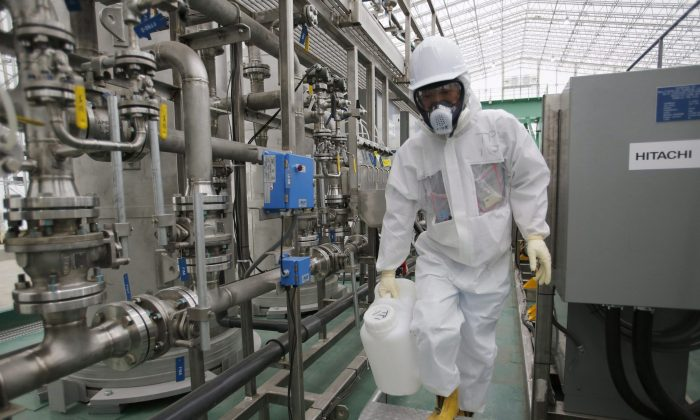 A Tokyo Electric Power Co. employee wearing radioactive protective gear works by the Advanced Liquid Processing Systems at the Fukushima Dai-ichi nuclear power plant in Okuma, Japan, Nov. 12, 2014. (AP Photo/Shizuo Kambayashi, Pool, File)