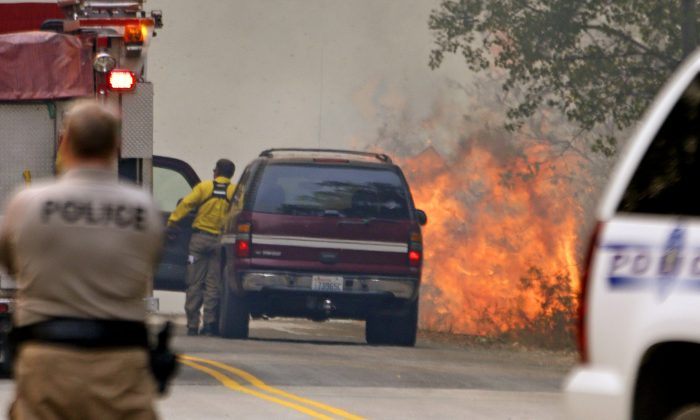 Flames kick up beside a road as firefighters respond to the flare-up Thursday, Aug. 20, 2015, in Twisp, Wash, a day after three firefighters were killed fighting a wildfire near the town. (AP Photo/Elaine Thompson)
