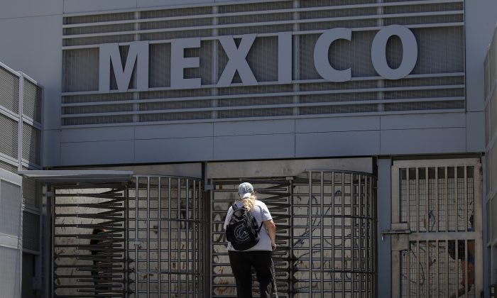 In this Aug. 18, 2015, photo, a woman approaches the entrance to the Mexico border crossing in San Ysidro, Calif. (AP Photo/Lenny Ignelzi)
