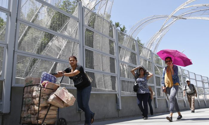 A woman pushes a cart full of goods as she and others head toward the entrance to the Mexico border crossing in San Ysidro, Calif., on Aug. 18, 2015. (AP Photo/Lenny Ignelzi)