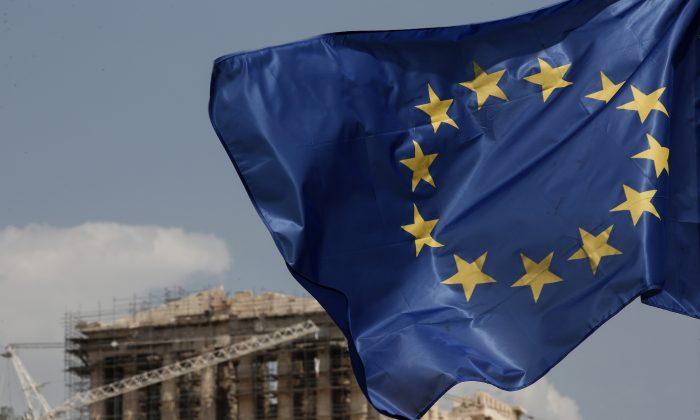 A European Union (EU) flag flutters in front of the temple of the Parthenon in Athens, Greece, Saturday, Aug. 15, 2015. (AP Photo/Yorgos Karahalis)