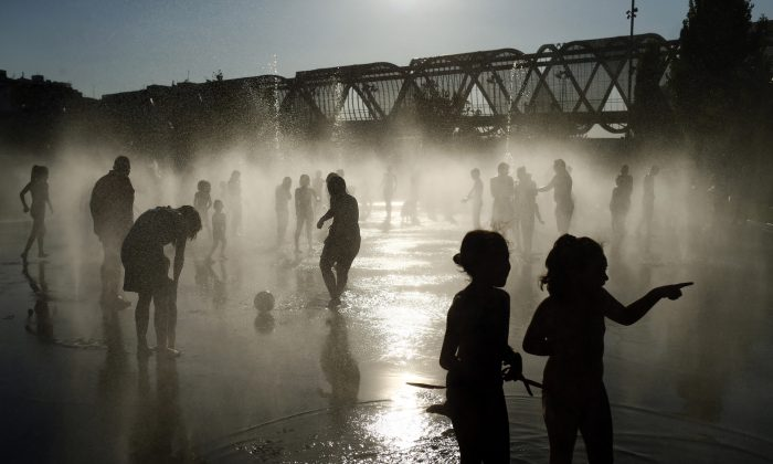 FILE - In this July 12, 2015 file photo, people cool down in a fountain beside the Manzanares river in Madrid, Spain. (AP Photo/Oscar del Pozo, File)
