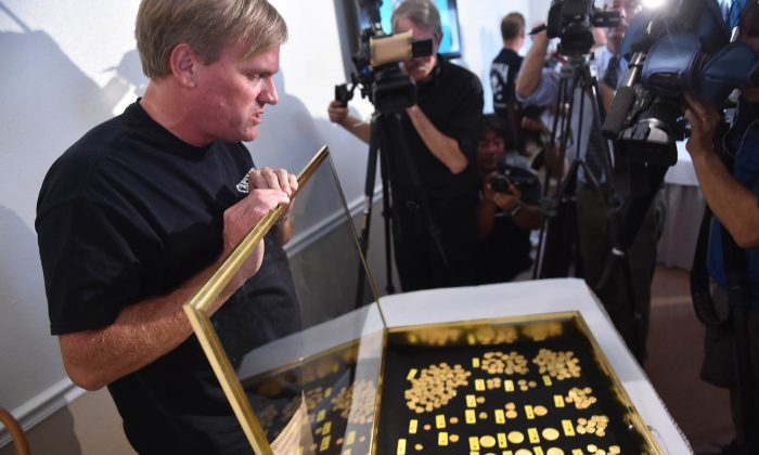 Treasure hunter Brent Brisben, captain and owner of 1715 Fleet - Queens Jewels LLC, displays their recent discovery of more than 350 gold coins valued at $4.5 million found off the coast of Wabasso Beach on July 30-31, 2015, during a news conference, Thursday, Aug. 20, 2015 in Sebastian, Fla. (Eric Hasert/The Stuart News via AP)