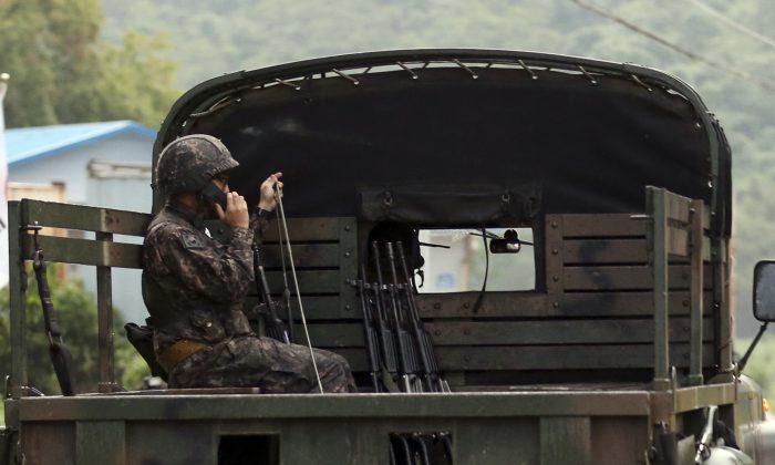 A South Korean soldier uses a radio on a military vehicle at the South Korean border town of Yeoncheon, South Korea, Thursday, Aug. 20, 2015. South Korea's military fired dozens of shells Thursday at rival North Korea after the North lobbed a single artillery round at the border town, the South's Defense ministry said. (Hong Hae-in/Yonhap via AP) KOREA OUT