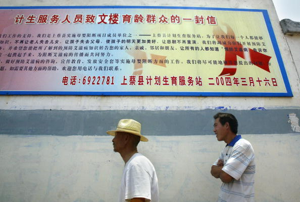 """WENLOU, CHINA: Farmers walk past an HIV/AIDS awareness board in Wenlou village, 28 May 2004, in central China&#039s Henan province, where US Ambassador to China Clark Randt paid a visit to open the USCDC/Global AIDS Program. The United Nations has described the epidemic in China as a """"ticking timebomb."""" (FREDERIC J. BROWN/AFP/Getty Images)"""