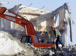 A worker stands by as an excavator scoops away the rubble of a building being demolished building in Beijing to make way for a new housing project. (AFP/Getty Images)