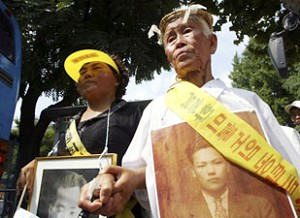 Korean family members of victims of World War II hold their relatives pictures during a march towards the Japanese embassy. (Chung Sung-Jun/Getty Images)