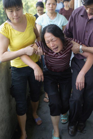 A relative of a trapped miner cries after a coalmine flood at the Daxing Colliery. A flood has trapped 102 workers underground in the mine, the official Xinhua News Agency reported in the latest accident to hit the world&#039s deadliest mining industry.  (China Photos/Getty Images)