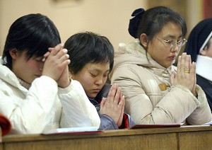 Chinese Catholics pray at the officially sanctioned Wangfujing Cathedral, as the communist regime continues a crackdown on underground churches and sects, in what some critics consider as one of the harshest crackdowns against underground Christians in years, with dozens of churches demolished and many worshippers arrested.  (Goh Chai Hin/AFP/Getty Images)