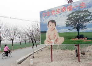 A woman cycles past a billboard encouraging couples to have only one child, along a road leading to a village in the suburbs of Beijing in this file photo. (Goh Chai Hin/AFP/Getty Images)