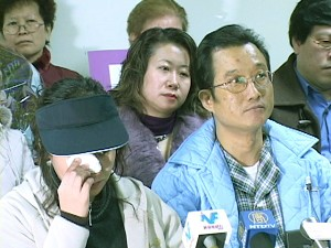 Ho's wife stands by his side during the press conference, wiping her tears. (The Epoch Times)