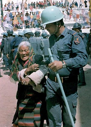 An injured Tibetan woman is taken away by a riot policeman in Kathmandu, Nepal, during a demonstration to mark the 36th anniversary of the uprising against Chinese occupation in Tibet, March 10, 2007. (Devendra M Singh/AFP/Getty Images)