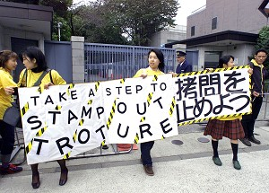 Japanese members of Amnesty International hold a banner in protest against use of torture at the entrance to the Chinese Embassy in Tokyo. (Kazuhiro Nogi/AFP/Getty Images)