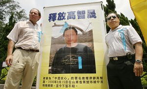 Edward McMillan-Scott (L) Vice President, European Parliament poses for pictures with Democracy Legislator Albert Ho next to a portrait of mainland jailed human rights lawyer Gao Zhisheng in Hong Kong, August 2006.  (Mike Clarke/AFP/Getty Images)