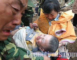 Little Langzhen's grandparents weep with relief upon seeing their grandson rescued from amidst the rubble, May 13, in Mianyang City, Beichuan County, Sichuan. (The Epoch Times)