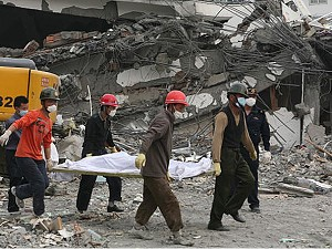 Rescuers carry a dead body past the debris of a collapsed houses on May 16, 2008 in Dujiangyan, one of the hard-hit cities, of Sichuan Province, China. (China Photos/Getty Images)