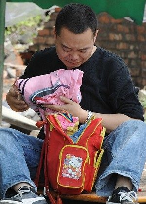 A father crying while looking through the school bag of his child. (MARK RALSTON/AFP/Getty Images)
