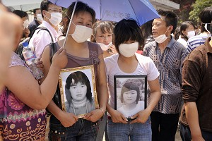 Mothers carry photos of their daughters who died when the Juyuan Middle School was destroyed in the devastating earthquake on Mat 12th. (Peter Parks/AFP/Getty Images)