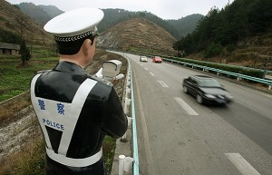A statue of a Chinese policeman holds a fully functioning speed gun, to catch speeding motorists on the Guiyang to Kaili expressway in Guizhou Province.  (Mark Ralston/AFP/Getty Images)
