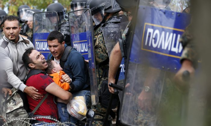 Migrant men help a fellow migrant man holding a boy as they are stuck between Macedonian riot police officers and migrants during a clash near the border train station of Idomeni, northern Greece, as they wait to be allowed by the Macedonian police to cross the border from Greece to Macedonia, Friday, Aug. 21, 2015.   (AP Photo/Darko Vojinovic)