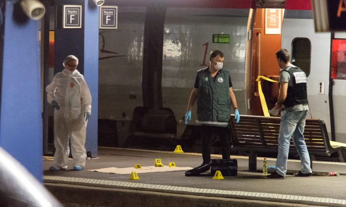 Police officers investigate on a platform next to a Thalys train at Arras train station, northern France, Friday, Aug. 21, 2015. (AP Photo)