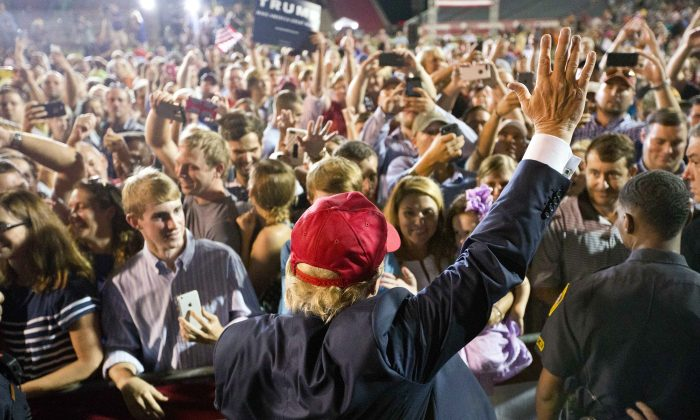 Republican presidential candidate Donald Trump waves to the crowd during a campaign pep rally, Friday, Aug. 21, 2015, in Mobile, Ala. (AP Photo/Brynn Anderson)