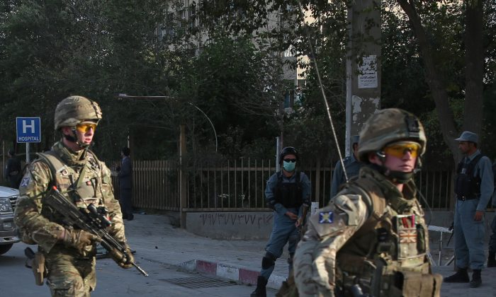 British soldiers leave the site of a suicide attack in the heart of Kabul, Afghanistan, Saturday, Aug. 22, 2015. The suicide car bomber attacked a NATO convoy traveling through a crowded neighborhood in Afghanistan's capital Saturday, killing at least 10 people, including three NATO contractors, authorities said. (AP Photo/Massoud Hossaini)