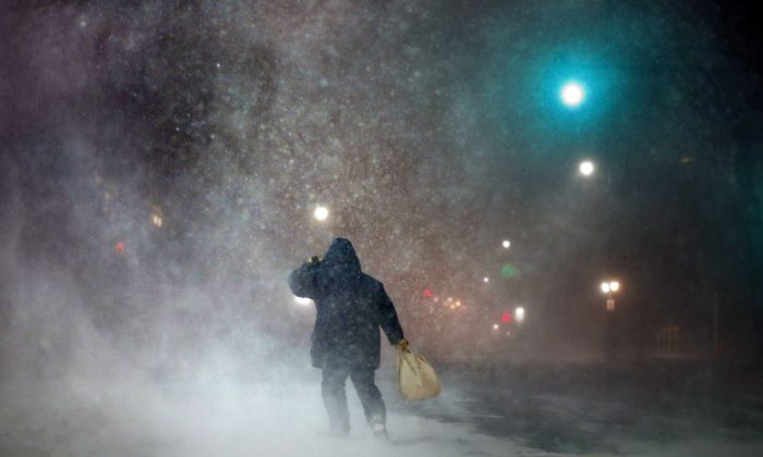 "FILE- In a Tuesday, Jan 27, 2015 file photo, a man battles fierce headwinds as he walks on Congress Street in Portland, Maine, during a blizzard. The editors of the Maine-based Farmers' Almanac have dubbed their latest forecast a ""winter deja vu,"" hearkening to last winter's misery across the Northeast (AP Photo/Robert F. Bukaty)"