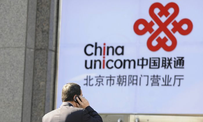 An office worker talks on a mobile phone in front of a China Unicom logo, California-based Apple's partner in China, in Beijing on January 5, 2012. (Liu Jin/AFP/Getty Images)