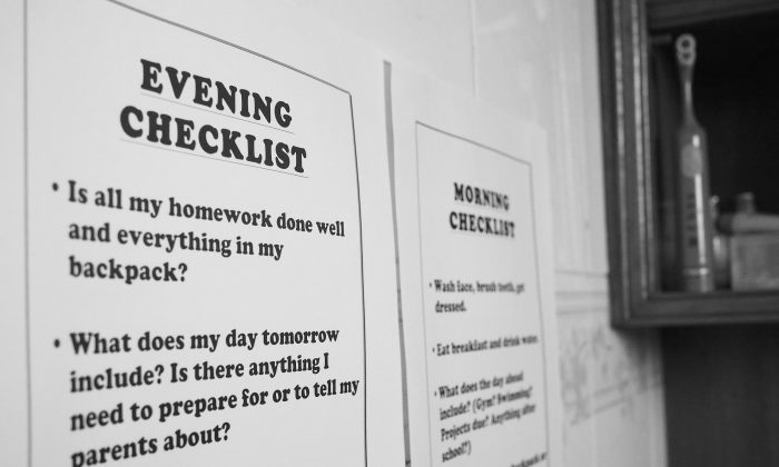 In this Sunday, Aug. 16, 2015 photo, these checklists, posted on a bathroom wall to keep an 8-year-old boy on track, help the third-grader to get organized on school nights and stay on task in the mornings. (AP Photo/Ted Anthony)