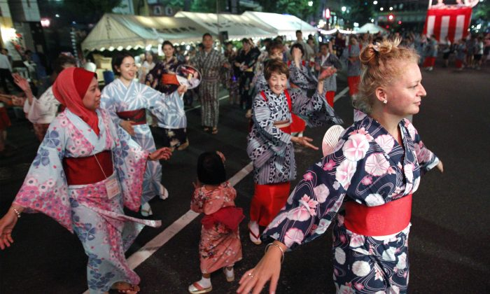 """In this Aug. 1, 2015, photo, foreign participants dance the traditional Japanese """"bon odori"""" with locals in Tokyo. (AP Photo/Ken Aragaki)"""