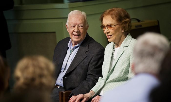 Former President Jimmy Carter, left, sits with his wife Rosalynn as they pose for photos after Carter taught Sunday School class at Maranatha Baptist Church in his hometown Sunday, Aug. 23, 2015, in Plains, Ga. (AP Photo/David Goldman)