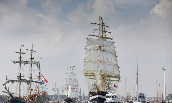Russian tall ship the Kruzenshtern, center right, arrives in Amsterdam, Netherlands, Wednesday, Aug. 19, 2015, to participate in SAIL Amsterdam 2015, a five-yearly festival celebrating the Dutch capital's maritime history that is expected to draw some 2 million visitors. (AP Photo/Phil Nijhuis)