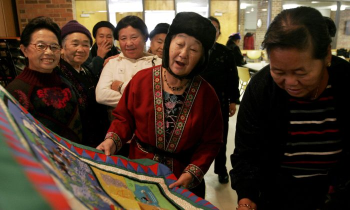 Hmong immigrants take a look at a Hmong story cloth that promotes seasonal safety tips at the Volunteers of America building, in Minneapolis, Minn., on Dec. 7, 2005. (AP Photo/Beth Schlanker)
