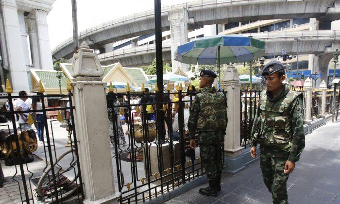 Thai soldiers walk outside the Erawan Shrine at Rajprasong intersection, the scene of last week's bombing, in Bangkok, Thailand, Monday, Aug. 24, 2015. (AP Photo/Sakchai Lalit)