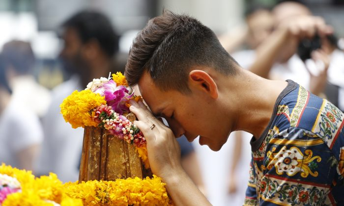 A man prays at the Erawan Shrine at Rajprasong intersection, the scene of last week's bombing, in Bangkok, Thailand, Monday, Aug. 24, 2015. (AP Photo/Sakchai Lalit)