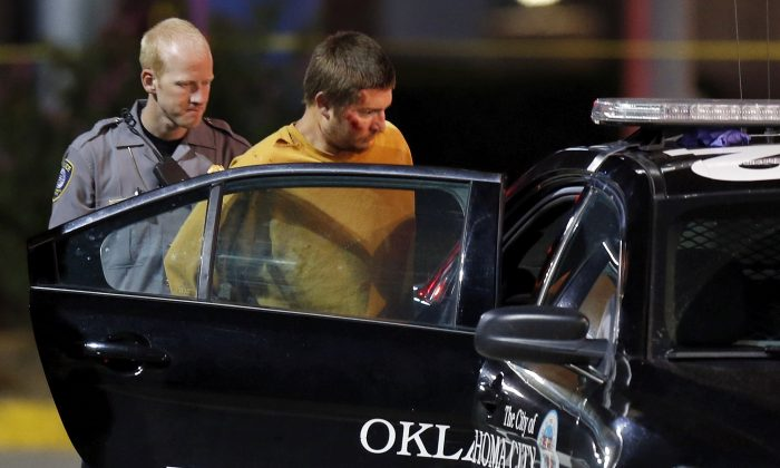 Christian Costello, son of Oklahoma Labor Commissioner Mark Costello, is placed in a police car, Sunday, Aug. 23, 2015, at the scene where Mark Costello was fatally stabbed in Oklahoma City. Christian Costello was arrested on a first-degree murder complaint, police said. (Nate Billings/The Oklahoman via AP) LOCAL STATIONS OUT (KFOR, KOCO, KWTV, KOKH, KAUT OUT); LOCAL WEBSITES OUT; LOCAL PRINT OUT (EDMOND SUN OUT, OKLAHOMA GAZETTE OUT) TABLOIDS OUT; MANDATORY CREDIT