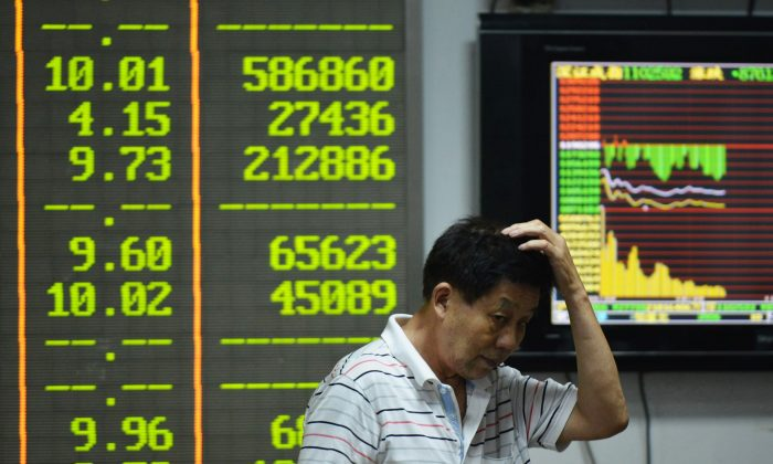 An investor gestures in front of screens showing share prices at a securities firm in Hangzhou, in eastern China's Zhejiang province on Aug. 24, 2015. (STR/AFP/Getty Images)