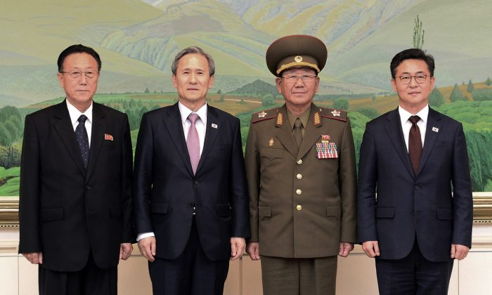 South Korean Unification Minister Hong Yong-pyo (R) and presidential security adviser Kim Kwan-jin (2L) with Kim Yang Gon (2R), a senior North Korean official responsible for South Korean affairs, and Hwang Pyong So (L), North Korea' top political officer for the Korean People's Army, after their meeting at the border village of Panmunjom, in Paju, South Korea, on Aug. 25, 2015. South Korea has agreed to halt propaganda broadcasts at noon Tuesday after North Korea expressed regret over a recent land mine blast that maimed two South Korean troops, both Koreas announced after three days of intense talks aimed at defusing soaring tension between the rivals. (South Korean Unification Ministry via AP)