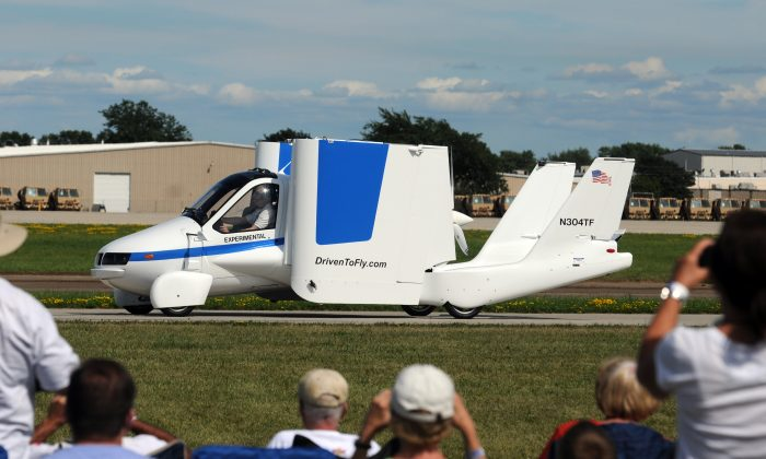 """In this Monday, July 29, 2013 photo, the Terrafugia """"roadable plane"""" folds up its wings after flying at the Experimental Aircraft Association's AirVenture in Oshkosh, Wis. (Joe Sienkiewicz/The Oshkosh Northwestern via AP)"""