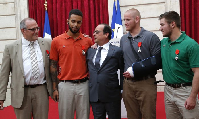 From the left, British businessman Chris Norman, Anthony Sadler, a senior at Sacramento State University in California, French President Francois Hollande, U.S. Airman Spencer Stone, and Alek Skarlatos a U.S. National Guardsman from Roseburg, Ore., pose at the Elysee Palace, Monday, Aug. 24, 2015 in Paris, France. (AP Photo/Michel Euler, Pool)