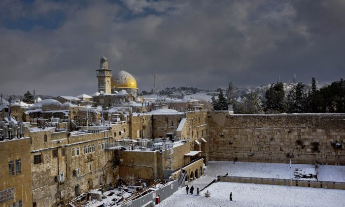 In this Friday, Dec. 13, 2013, file photo, the Western Wall and the Dome of the Rock, some of the holiest sites for for Jews and Muslims, are covered in snow in Jerusalem. (AP Photo/Dusan Vranic)