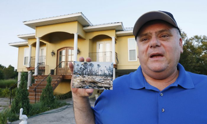 In this July 23, 2015 photo, Efrem Garza stands before his new home built on the lot of his previous house that was destroyed by Hurricane Katrina and holds a photograph taken by a friend of the remains of that house on South Seashore Avenue in Long Beach, Miss. (AP Photo/Rogelio V. Solis)