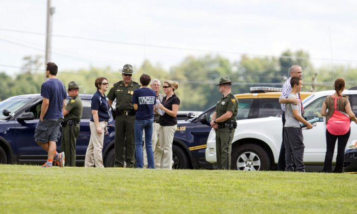 """West Virginia Police and school officials help parents reunite with their children at Philip Barbour High School following a """"hostage-type situation"""" Tuesday, Aug. 25, 2015, in Philippi, W.Va. (AP Photo/Ben Queen)"""