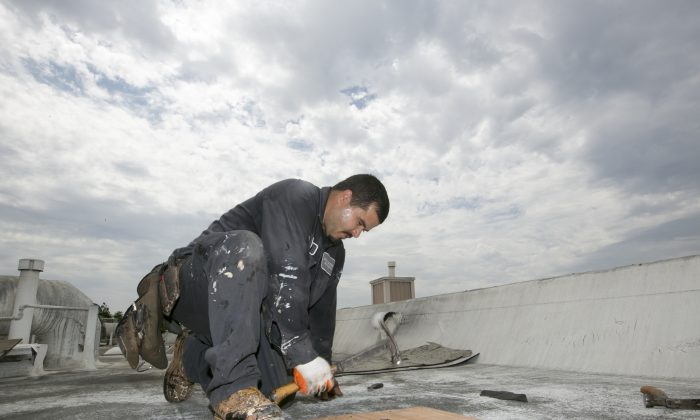 Roofer Joel Camberos with Hull Brothers Roofing & Waterproofing resurface townhomes roofs at the Marina del Rey seaside community of Los Angeles on Tuesday, Aug. 25, 2015. (AP Photo/Damian Dovarganes)