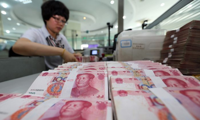 A teller counts yuan banknotes in a bank in Lianyungang, east China's Jiangsu province on August 11, 2015. (STR/AFP/Getty Images)
