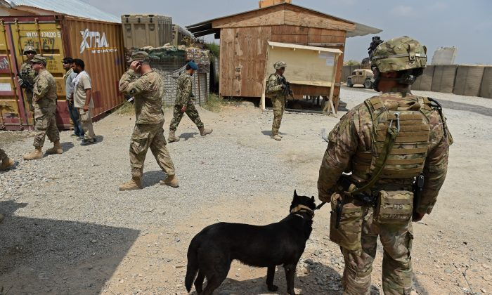 In this photograph taken on August 14, 2015, a US army soldier and military dog keep watch as Afghan National Army (ANA) soldiers walk through coalition force Forward Operating Base (FOB) Connelly in the Khogyani district in the eastern province of Nangarhar. (Wakil  Kohsar/AFP/Getty Images)
