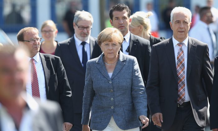 German Chancellor Angela Merkel, flanked by Heidenau Mayor Juergen Opitz and Saxony Governor Stanislaw Tillich, arrives to speak to the media after spending over an hour visiting the aslyum shelter that was the focus of recent violent protests on August 26, 2015 in Heidenau, Germany. (Sean Gallup/Getty Images)